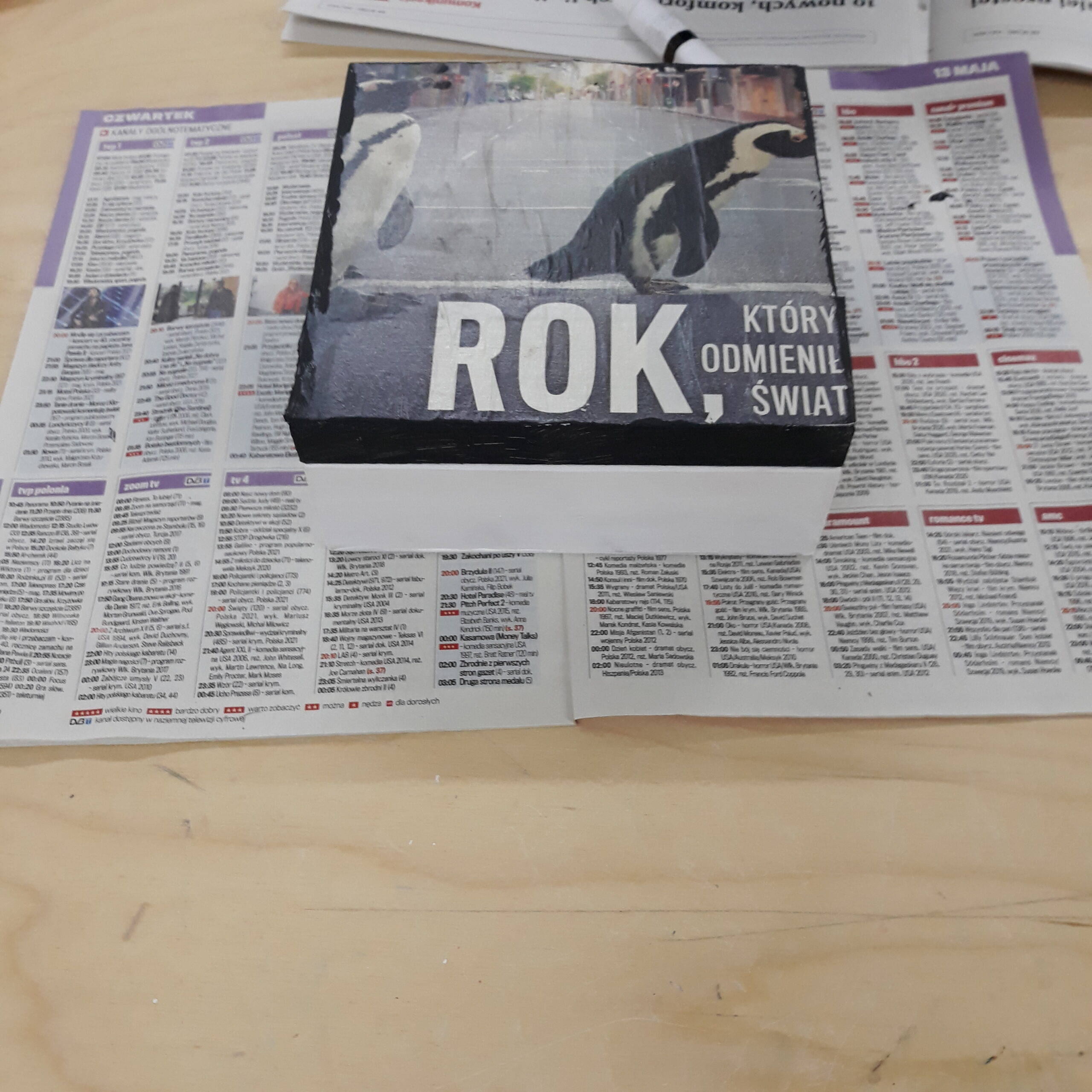 Pudełko ozdobione wycinkiem z gazety na którym jest słowo ROK