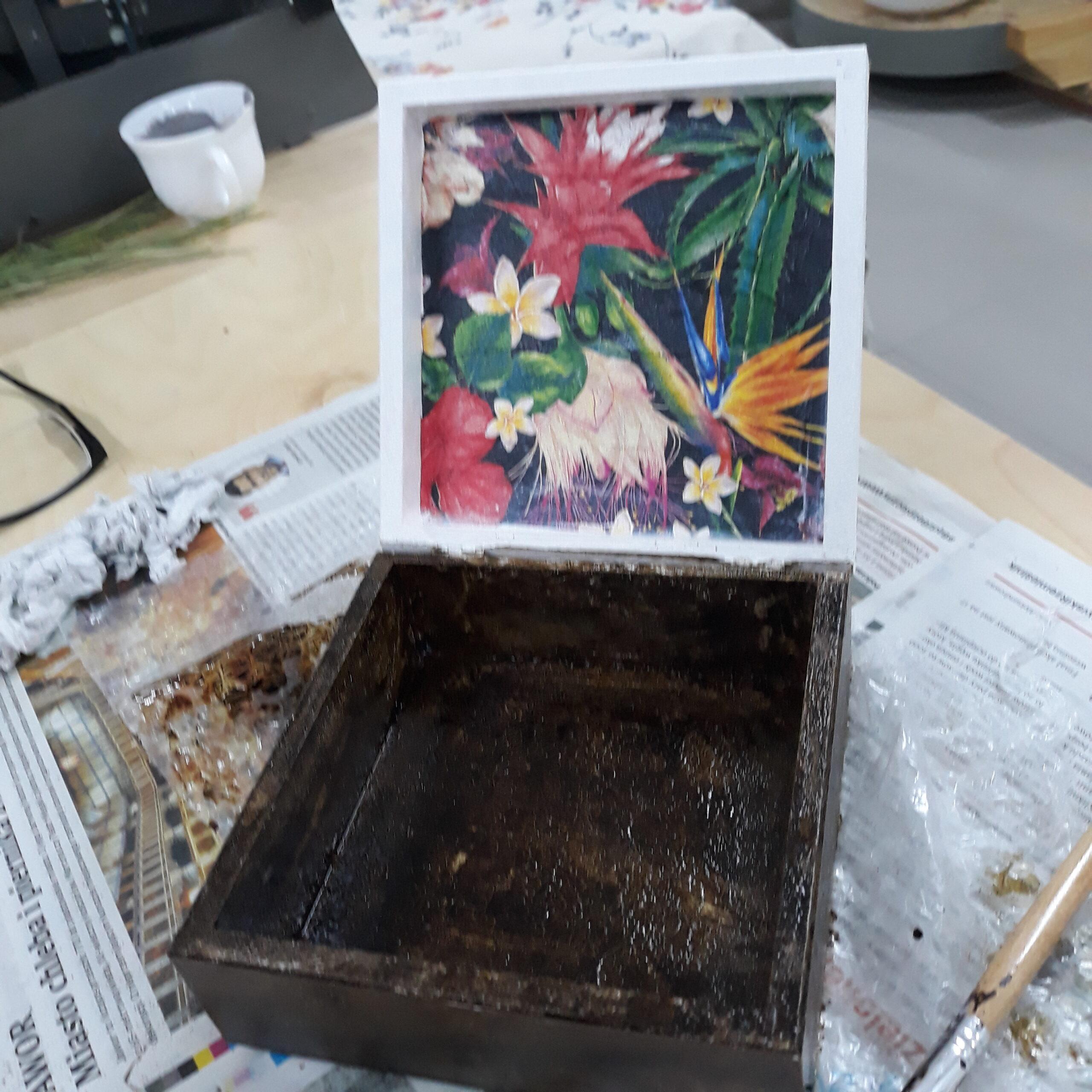 Otwarte brązowe pudełko które na wnętrzu wieka ma kwiatowy wzór