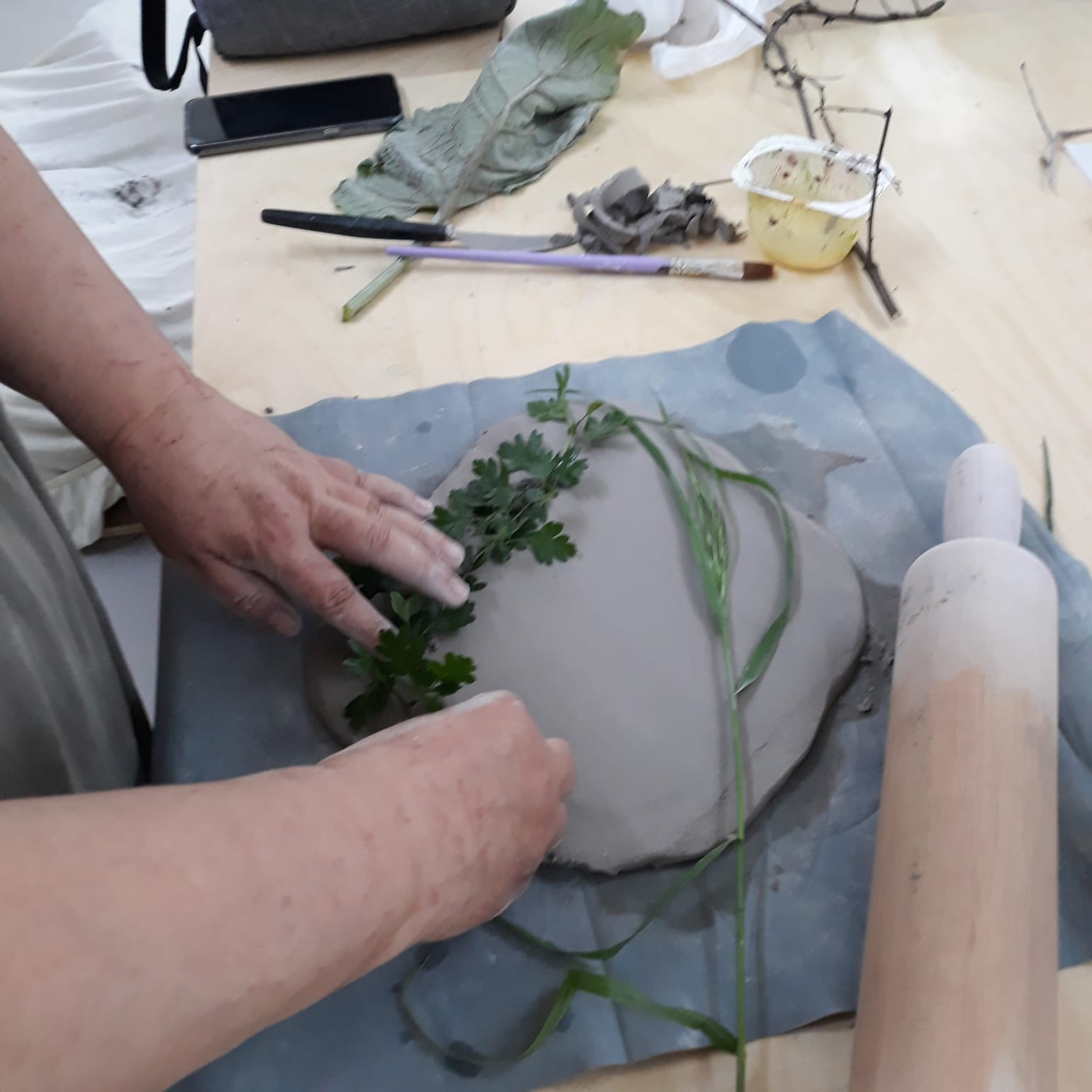 taca gliniana z odbitą w niej rośliną